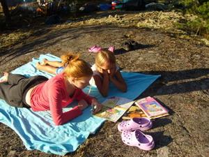 Två barn som ligger ned på en fil och läser en tidning